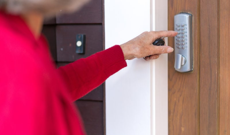 Senior woman uses keypad on digital lock to unlock and open domestic front door