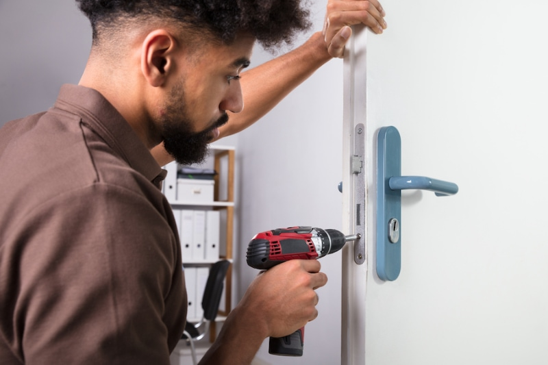 Close-up Of A Young Male Carpenter Installing Door Lock With Wireless Screwdriver